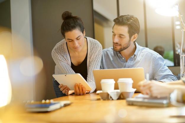 Colegas atractivos compartiendo ideas de negocios en espacio de trabajo.