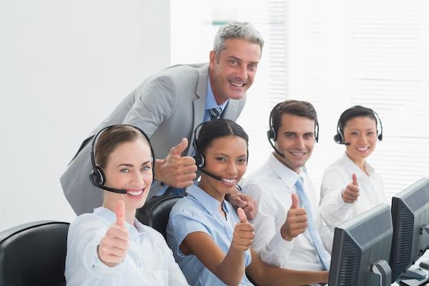 Colegas con auriculares usando computadoras mientras gesticulan pulgares arriba