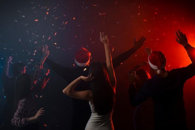 Colegas bailando en confeti en la fiesta de año nuevo