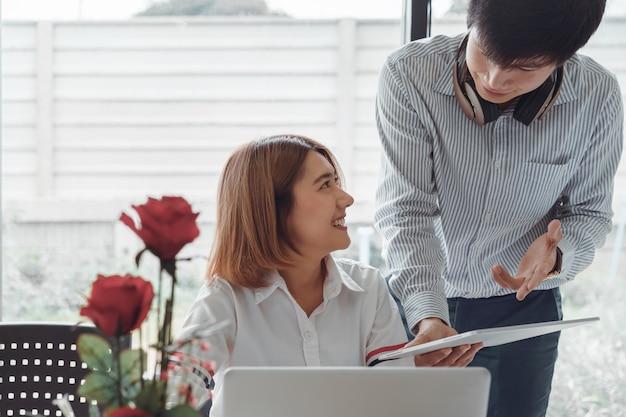 Los colegas caucásicos asiáticos jovenes de lanzamiento que discuten el trabajo juntos en la tableta, trabajador de sexo masculino que habla con el concepto femenino de la colaboración del compañero de trabajo