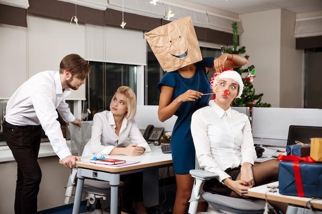 Colegas celebrando la fiesta de navidad en la oficina bebiendo champán sonriendo.