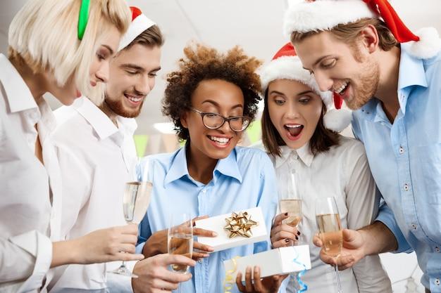 Colegas celebrando la fiesta de navidad en la oficina sonriendo dando regalos.
