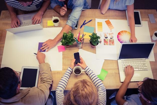 Colegas creativos con computadora portátil y tableta digital