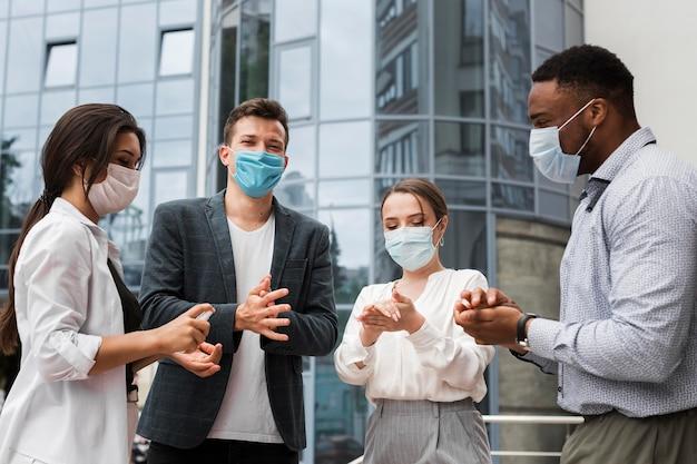Colegas desinfectando las manos al aire libre durante una pandemia mientras usan máscaras