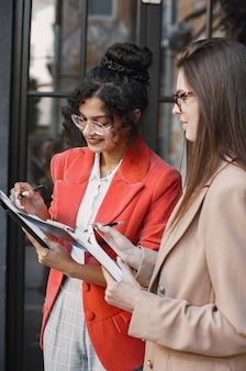 Colegas discutiendo datos en el café al aire libre. mujeres multirraciales que analizan la estrategia productiva para la proyección empresarial utilizando documentos en street cafe