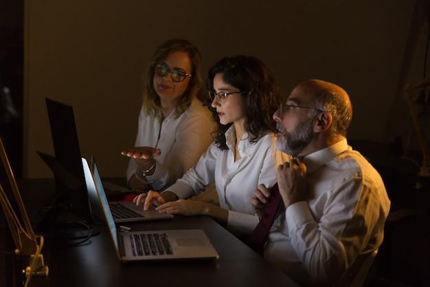Colegas discutiendo el trabajo en la oscura oficina