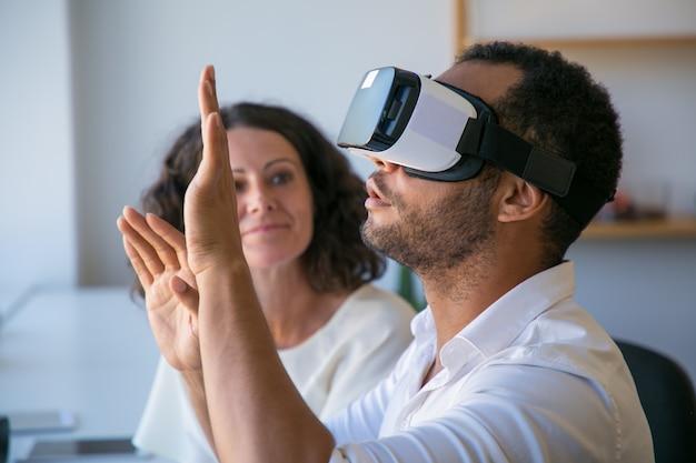 Colegas emocionados que prueban el simulador de realidad virtual juntos
