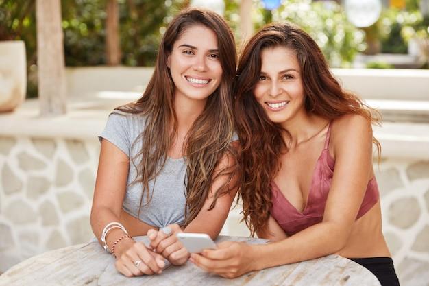 Las colegas femeninas felices y positivas pasan juntos el descanso del trabajo, diviértanse como blogs en las redes sociales a través del teléfono celular, tengan tiempo libre en la cafetería