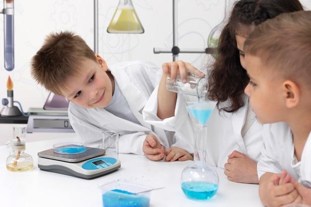 Colegas haciendo un experimento químico en la escuela.