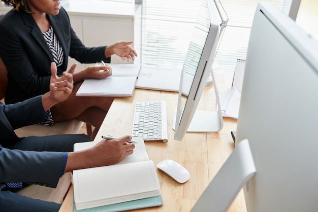 Colegas irreconocibles mirando la pantalla de la computadora juntos en la oficina