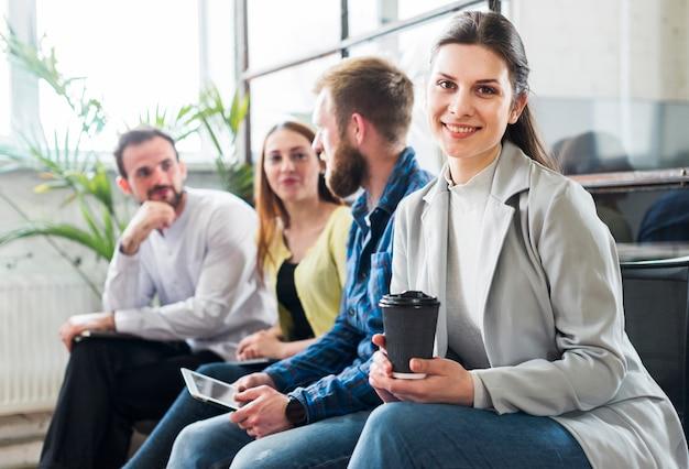 Colegas jovenes del negocio que se sientan junto durante rotura en oficina