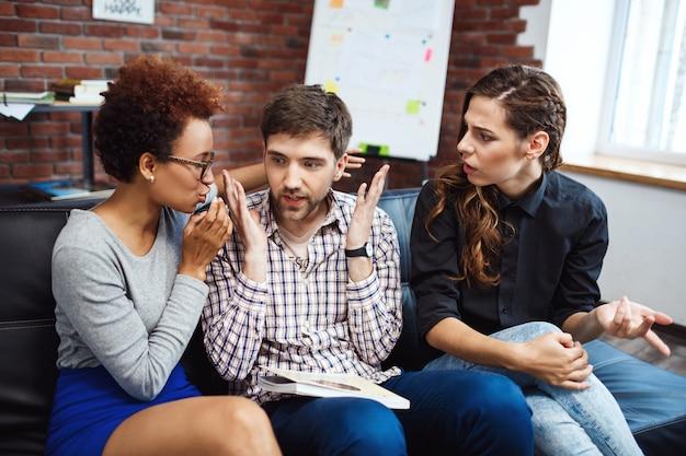 Los colegas jóvenes que se comunican durante el negocio frenan en la oficina.