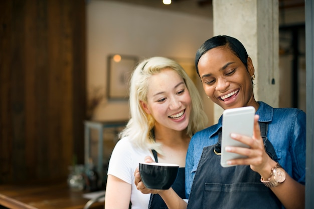 Colegas jugando en un teléfono en una cafetería