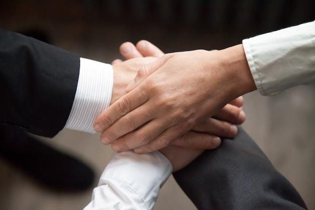 Colegas juntando las manos motivando para obtener mejores resultados.