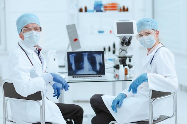 Colegas médicos sentados en una mesa en el laboratorio