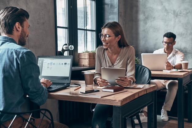 Colegas modernos en ropa casual elegante que se comunican juntos y usan tecnologías