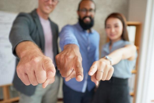 Colegas multiétnicos de pie en la oficina con los brazos extendidos y apuntando al punto