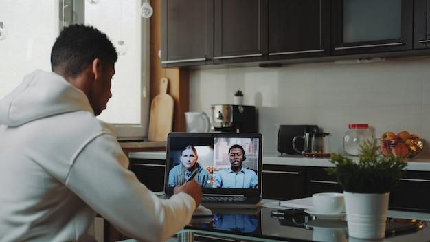 Colegas multirraciales que trabajan desde su casa en cuarentena haciendo video llamadas comunes por computadora