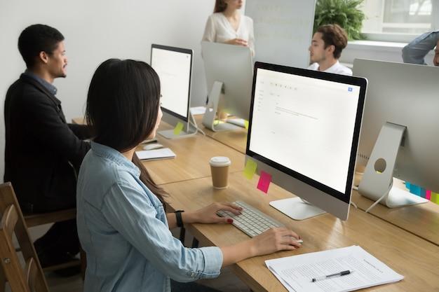 Colegas multirraciales trabajando juntos en computadoras de escritorio en oficina corporativa