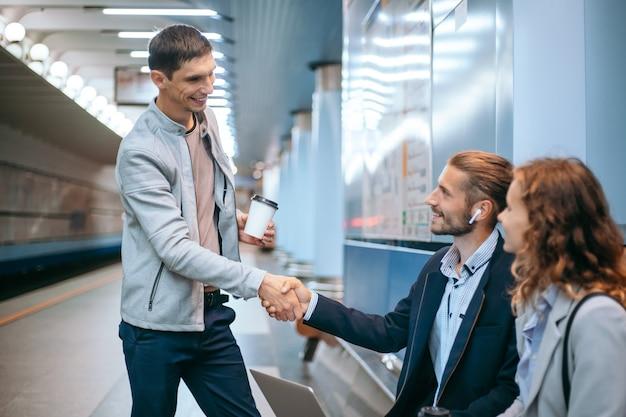 Colegas de negocios dándose la mano en la plataforma del metro