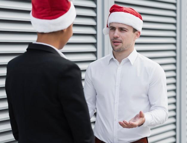 Colegas de negocios con sombreros de santa