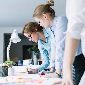 Colegas que preparan la tabla en el papel sobre el escritorio en la oficina moderna