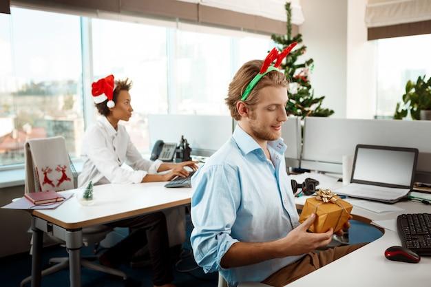 Colegas que trabajan en la oficina el día de navidad dando regalos.
