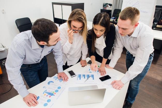 Colegas en una reunión de oficina hablando y trabajando en una computadora portátil