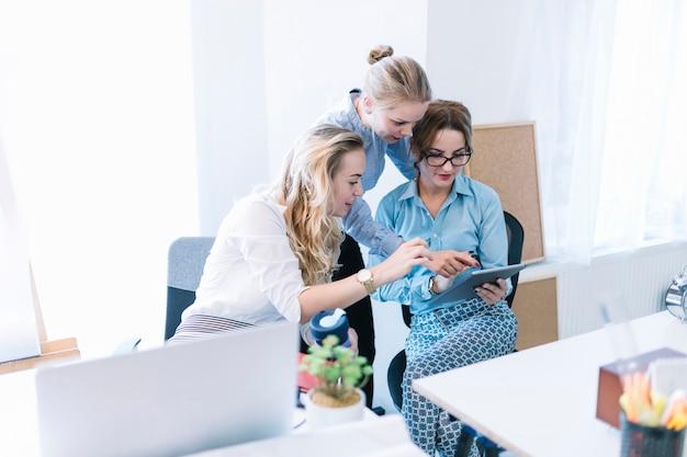 Colegas de sexo femenino que señalan y que miran la tableta digital en la oficina
