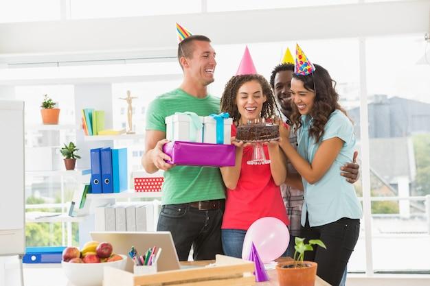 Colegas sonrientes que celebran cumpleaños en la oficina