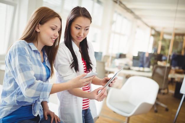Colegas con tableta digital y teléfono móvil en la oficina