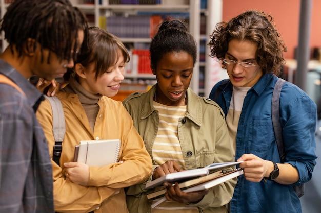 Colegas universitarios hablando en la biblioteca Foto gratis