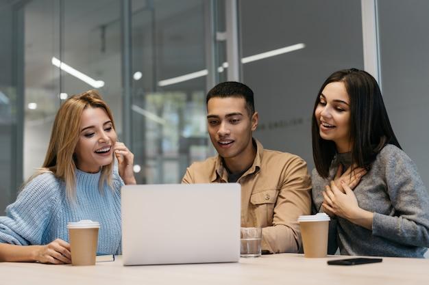 Colegas usando laptop, viendo cursos de capacitación, comunicación, trabajo en equipo.