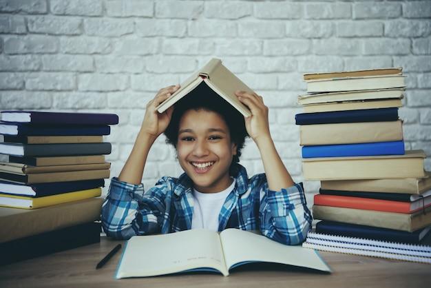 El colegial afroamericano sostiene el libro sobre la cabeza.