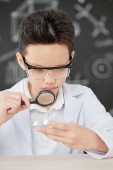 Colegial asiático curioso mirando placa de petri a través de una lupa