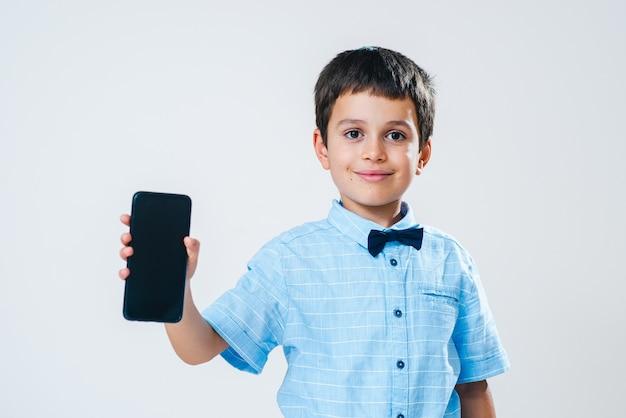 El colegial con una camisa con pajarita demuestra una pantalla de teléfono inteligente