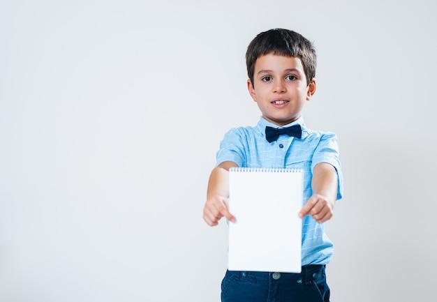 El colegial con una camisa con pajarita sostiene un cuaderno frente a él y lo apunta a la cámara.