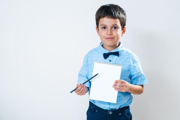 El colegial con una camisa con una pajarita sostiene un cuaderno frente a él y lo señala con un lápiz