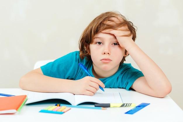 Colegial cansado sentado en la mesa. niño haciendo los deberes.
