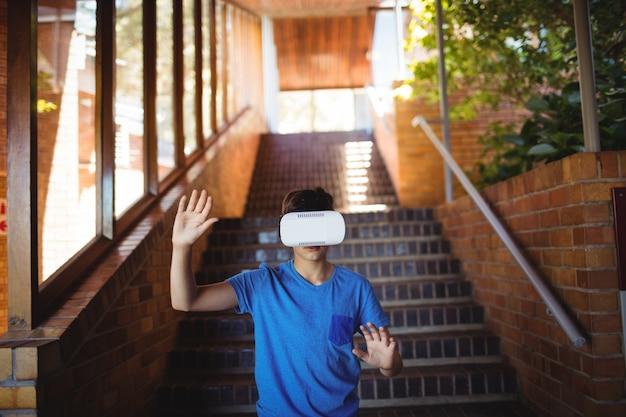 El colegial con casco de realidad virtual en escalera