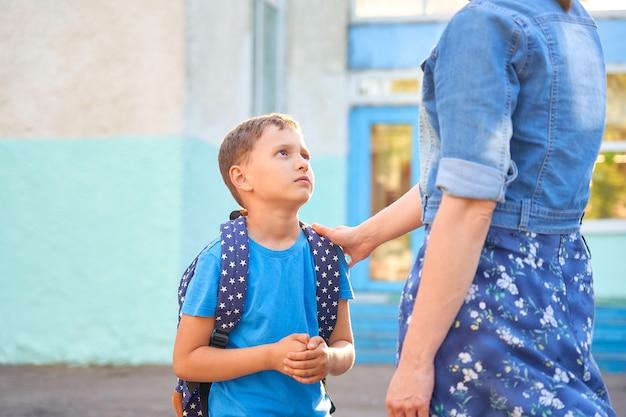 Colegial caucásico frustrado con una mochila mira con tristeza a su madre