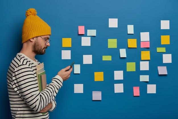 Un colegial elegante desplaza información en internet a través de un teléfono celular moderno, se para con libros en el interior, hace un plan estratégico, usa notas adhesivas para recordar material importante
