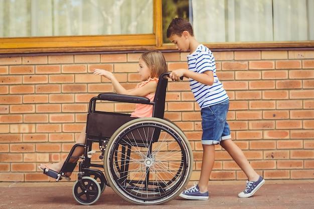 Colegial empujando a una niña en silla de ruedas