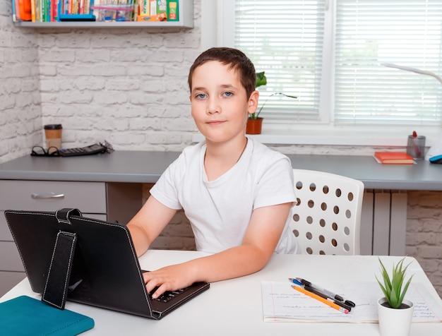 Colegial feliz haciendo los deberes y sentado en el escritorio. educación en casa