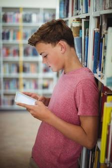 Colegial feliz con tableta digital en biblioteca