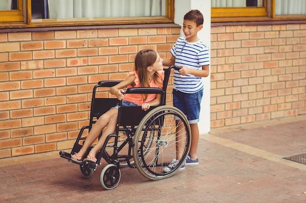 Colegial hablando con una niña en silla de ruedas