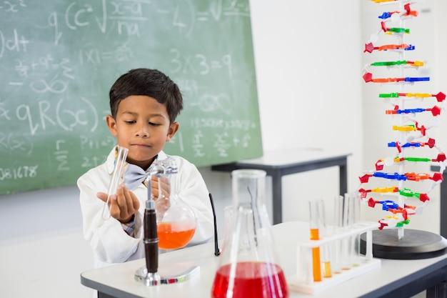 Colegial haciendo un experimento químico en laboratorio