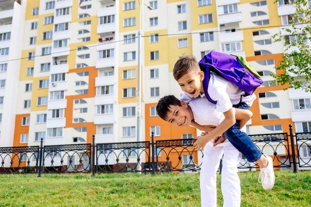 Un colegial lleva a su amigo en la espalda de camino a la escuela en la calle en un nuevo barrio