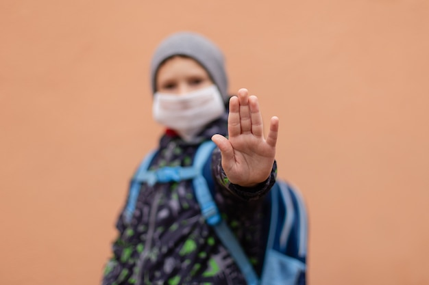 Un colegial con una máscara protectora muestra su mano stop