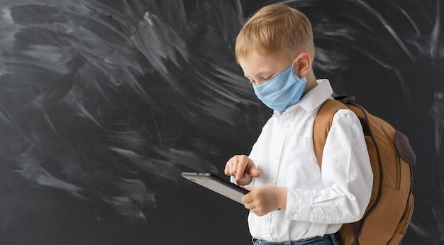 Un colegial moderno inteligente con una máscara protectora está parado cerca de la junta escolar. educación sobre cuarentena. educación primaria en una pandemia. el niño sostiene una tableta en sus manos y sonríe.